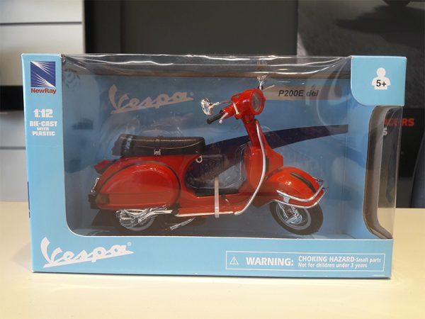 Miniatura de una moto Vespa modelo 1995 con su empaque original. Color rojo en una escala de 1:12