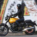 Moto guzzi v7 iii vista izquierda lejos color mostaza con una mujer manejando.