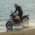 Hombre en la playa manejando una Moto Guzzi V85 TT