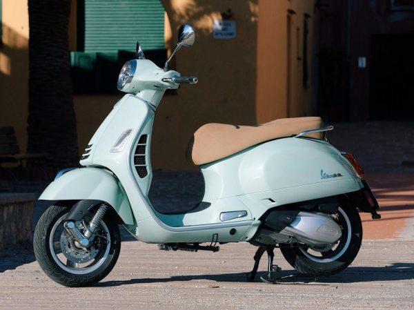 foto producto lateral izquierdo moto Vespa GTS 300 color celeste y el asiento color beige
