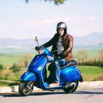 Foto producto frontal izquierda moto Vespa GTS 300 en color azul con un hombre manejándola