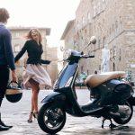 una pareja disfrutando la movilidad por la ciudad en una Vespa Primavera 150 color negra